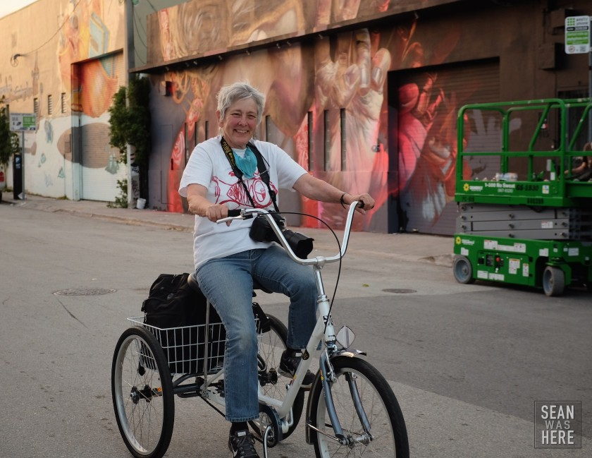 Martha Cooper riding her 3 wheeler documenting Wynwood. Background is Case Maclaim with a mural in progress. Wynwood Miami